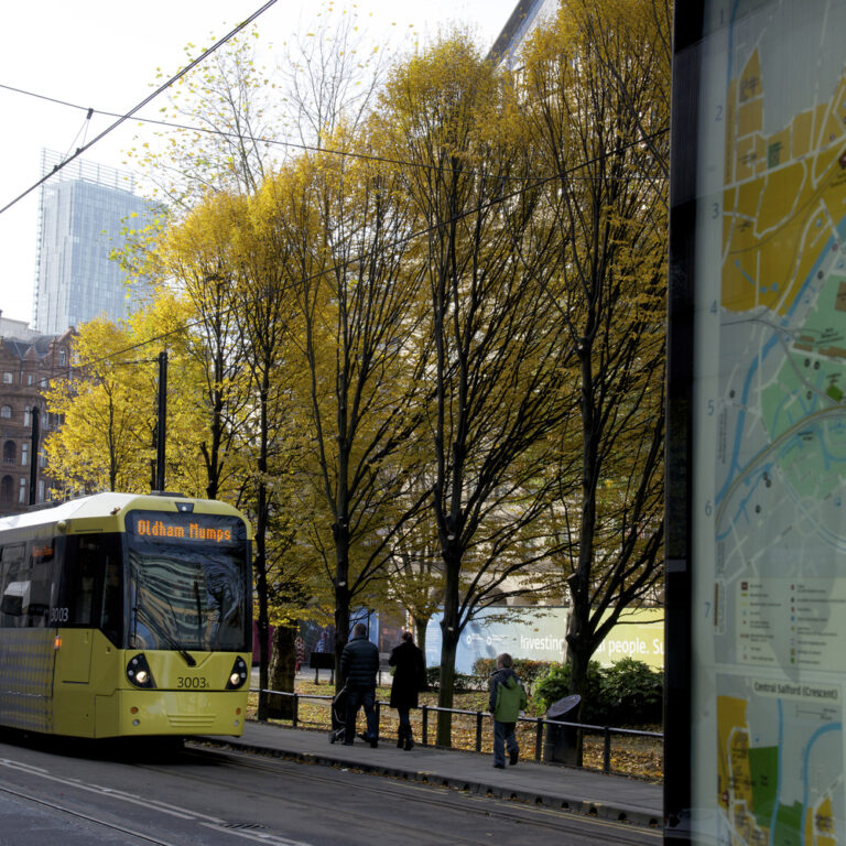 Manchester Tram next to map of Manchester